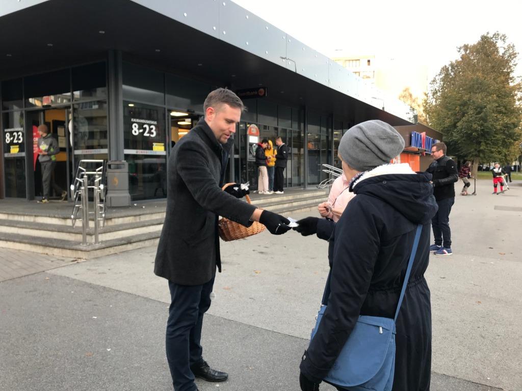 Linnaosavanem Andre Hanimägi helkureid jagamas