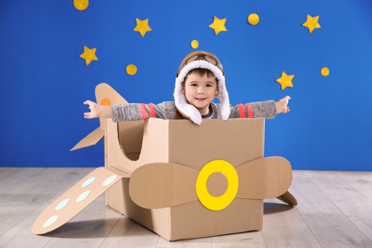 Cute,Little,Child,Playing,With,Cardboard,Airplane,Near,Blue,Wall