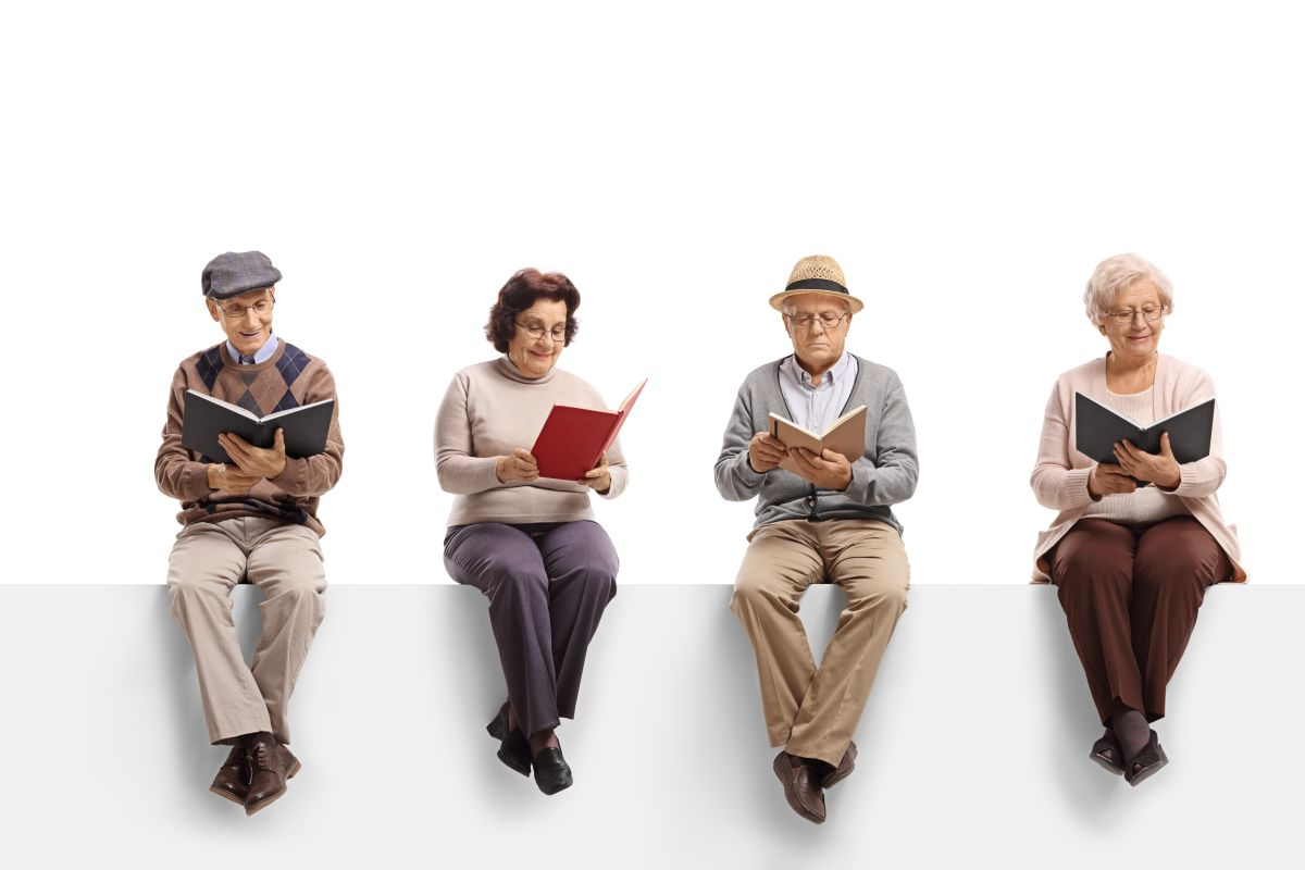 Group,Of,Elderly,People,Sitting,On,A,White,Panel,Reading