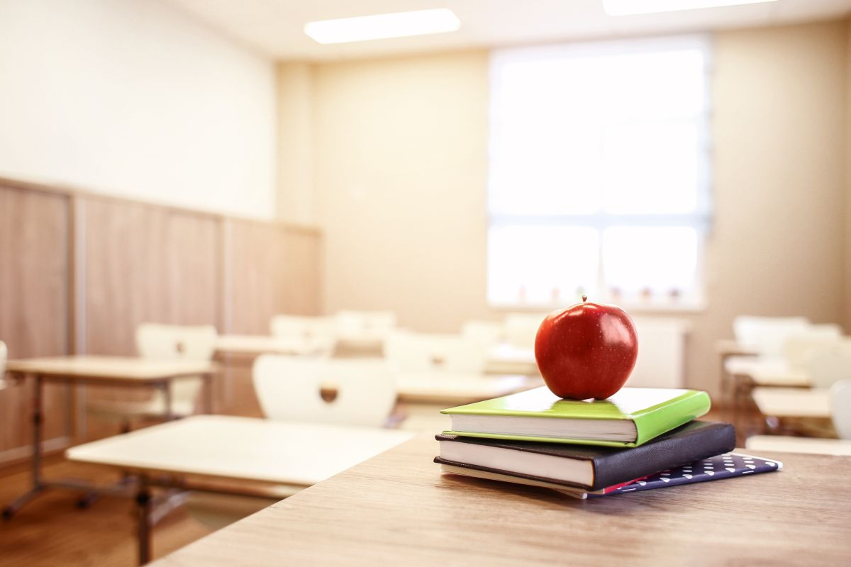 School,Teacher's,Desk,With,Stack,Of,Books,And,Apple