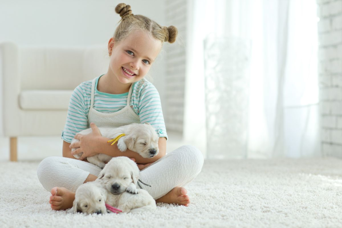 The,Child,With,A,Dog,Sitting,On,The,Carpet,At