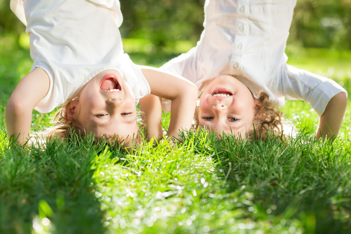 Happy,Children,Playing,Head,Over,Heels,On,Green,Grass,In
