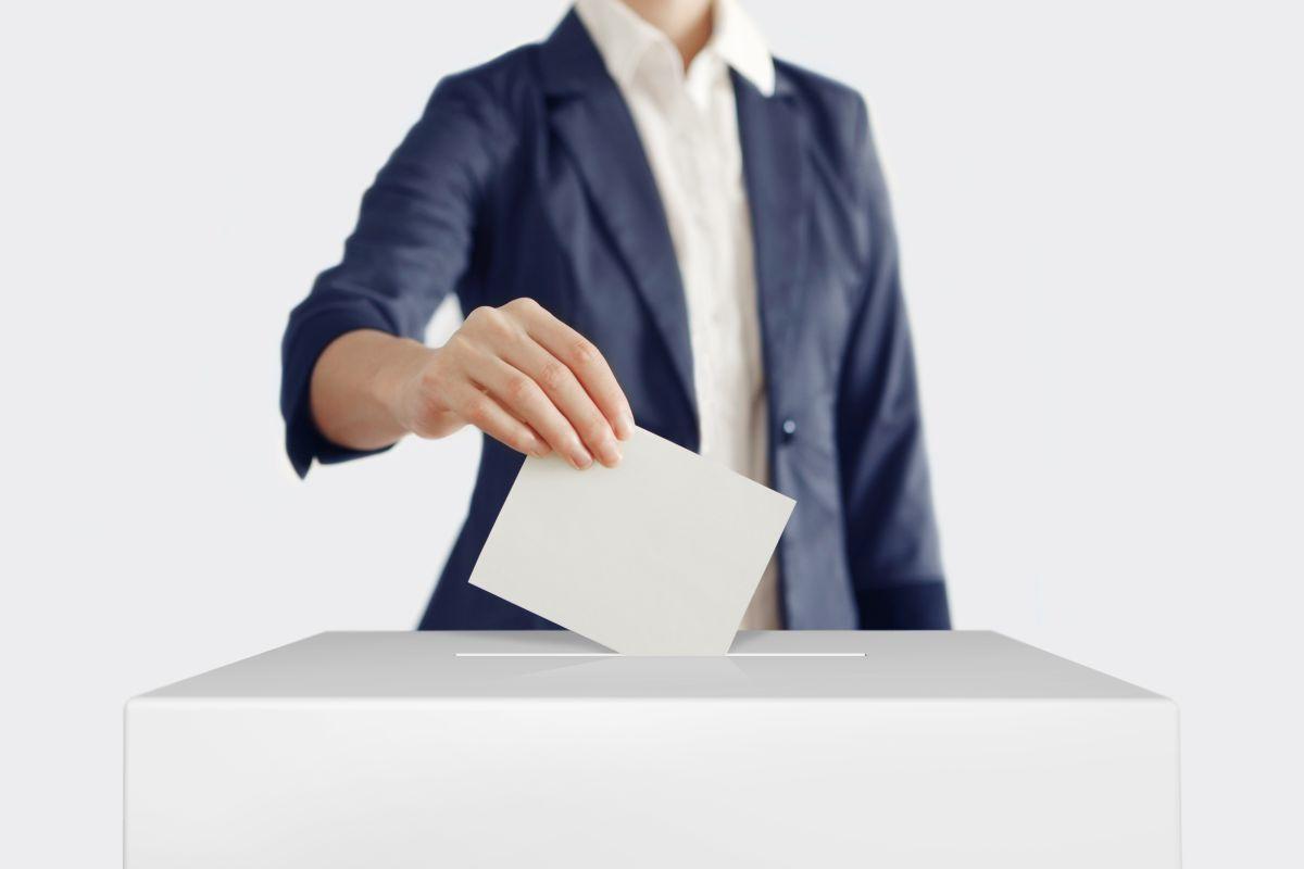 Woman,Putting,A,Ballot,Into,A,Voting,Box.